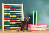 Toy abacus, books and pencils on table, on school desk background