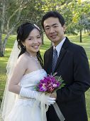 pic of wedding couple  - Wedding couple holding flower bouquet smiling in the park - JPG