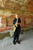Saxophone player performing under Central Park bridge in Manhattan