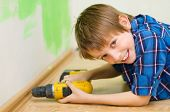 stock photo of plinth  - little boy worker installing plinth at home - JPG