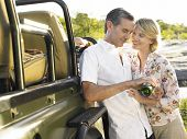 stock photo of  jeep  - Happy adult couple by jeep with man pouring wine in glass - JPG