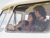 picture of campervan  - Smiling young couple in campervan view through window screen - JPG