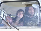 stock photo of campervan  - Smiling young couple in campervan during road trip - JPG
