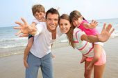picture of piggyback ride  - Parents giving piggyback ride to kids at the beach - JPG