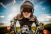 Biker in sunglasses and leather jacket racing on the road (fisheye lens)