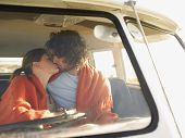 image of campervan  - Loving young couple kissing in campervan during roadtrip - JPG