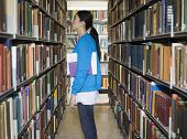 pic of shelving unit  - Side view of a young woman standing by bookshelf in library - JPG