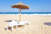 stock photo of lagos  - Thatched umbrella and beach chairs on the beach near Lagos Portugal - JPG