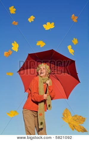 Happy Woman With Umbrella And Falling Yellow Leaves