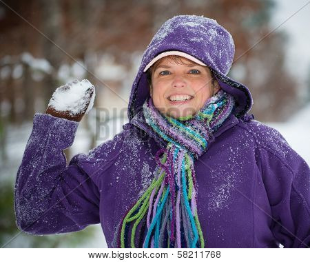 Woman playing in snow throwing snowball