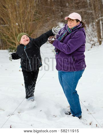 Mother and son playing in snow by having snowball fight