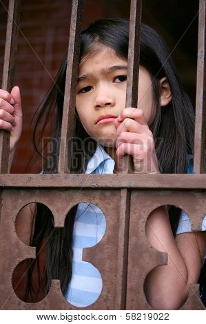 Little Girl Standing Behind Iron Bars