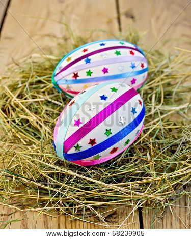 Easter Eggs With Ribbons And Sequins In The Hay