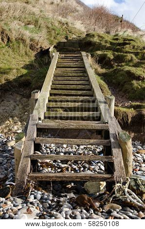 Wooden steps leading to a pebbled beach