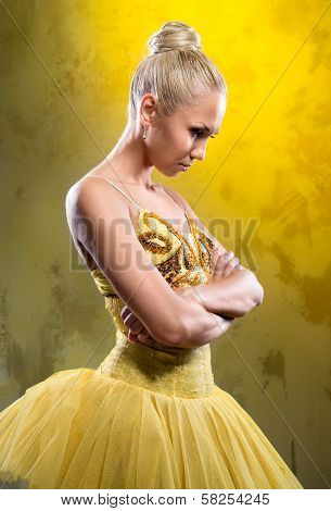 Sad Ballerina In Yellow Tutu Posing Over Obsolete Wall