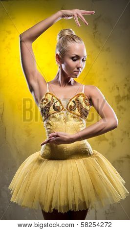Lovely Ballerina In Yellow Tutu Posing Over Obsolete Wall