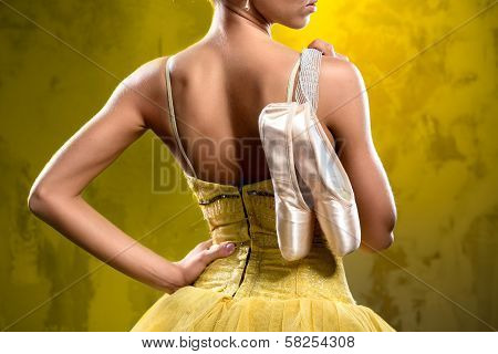 Ballerina With Pointe Shoes Against Obsolete Wall Background