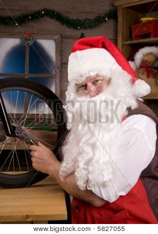 Santa Assemblying Bicycle In Workshop