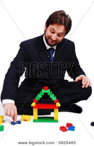 Young Mane Wearing Suit Is Making A House With Cubes Toys