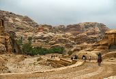 Tourists On Foot And On Horseback Visiting The Petra In Jordan