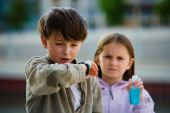 stock photo of avian flu  - Two children stand in an urban setting one sneezing into their elbow the other holding a bottle of soapless hand cleanser - JPG