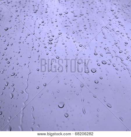 Water drops on glass in blue