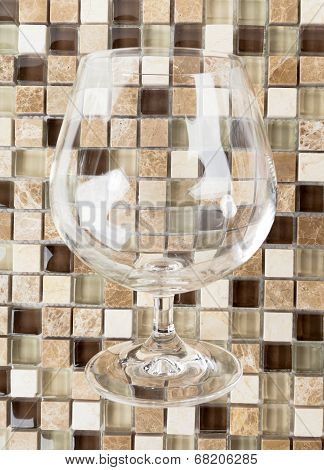 Empty Tumbler for whiskey or brandy over Mosaic Stones Background