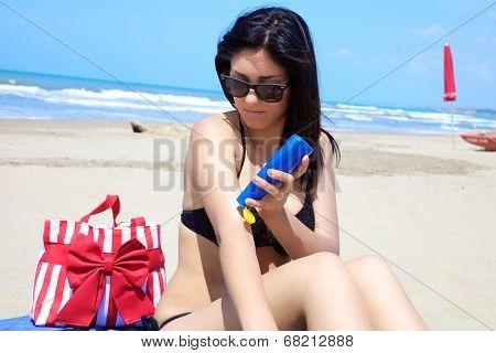Gorgeous Female Model Putting Sun Cream On Her Body On Tropical Beach