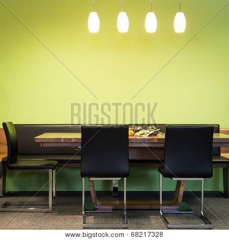 cantilever chairs at timber table with lamps and green wall