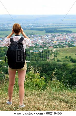 young woman hiking watching through binoculars