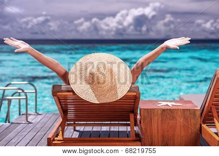 Luxury female tanning on the beach, wearing big stylish hat, enjoying beautiful seascape, summer fashion, travel and tourism concept