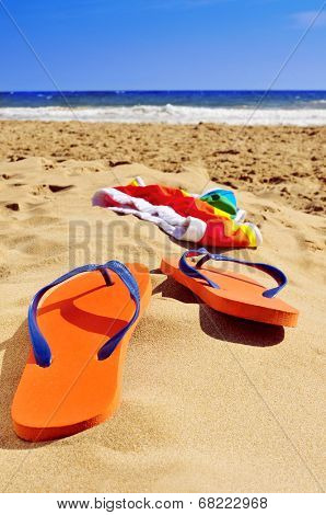 orange flip-flops and colorful swimsuit in the sand of a beach