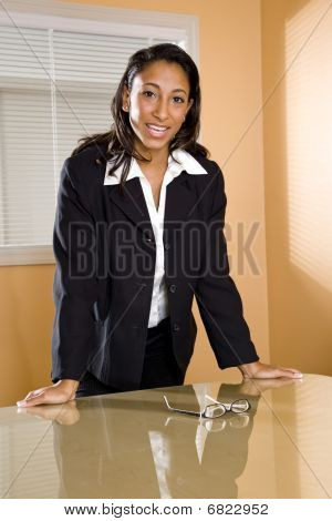 Young African-American female office worker standing in boardroom