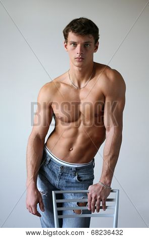 Young muscular man leaning on the chair