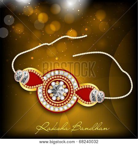 Beautiful rakhi on shiny brown background for Happy Raksha Bandhan celebrations.