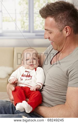 Proud father holding tiny baby in arms. My daddy is cool is written on baby's top.