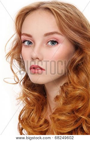 Portrait of young beautiful woman with long red curly hair and fresh make-up over white background
