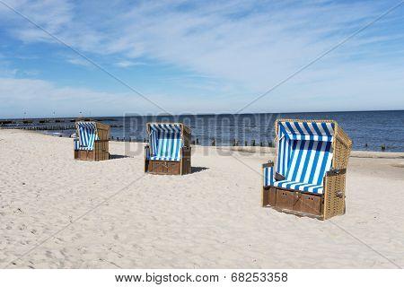 Empty sunbathing baskets on the beach.