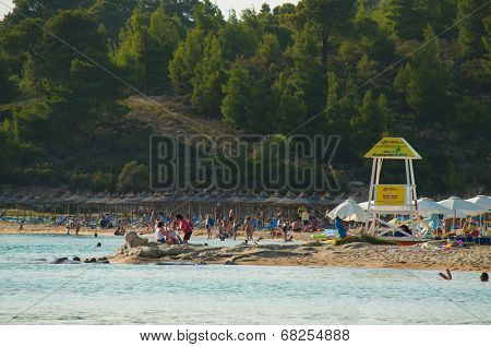GREECE - JUNE 27: Tourists enjoying on the beautiful beach and sunny day on June 27,2014 on the Kalogria Beach near Nikiti, on the west coast of Sithonia, Greece.