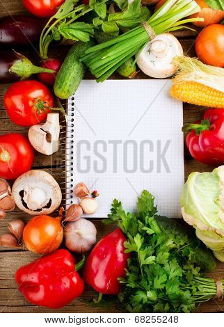 Fresh Organic Vegetables and Spices on a Wooden Background and Paper for Notes.Open Notebook and Fresh Vegetables Background. Diet. Dieting concept