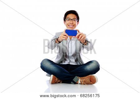 Happy asian man sitting on the floor and making photo on smartphone