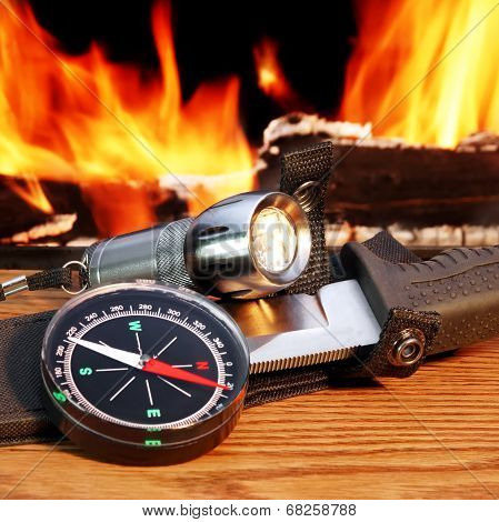 Compass,  Hunting Knife And  Flashlight. Campfire In Background.