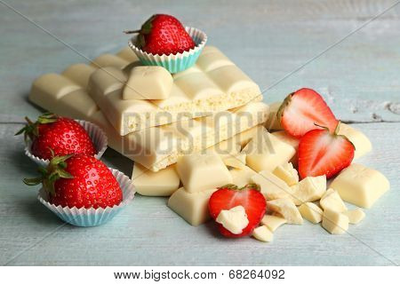 White chocolate bar with fresh strawberries, on color wooden background