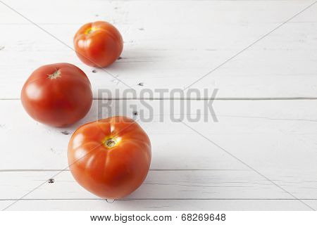 Three Tomatoes On A White Table
