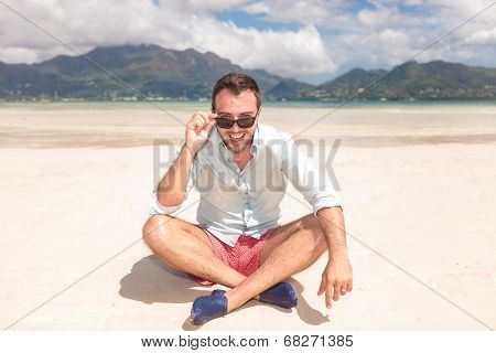 seated man on the beach looking at the camera while taking off his sunglasses