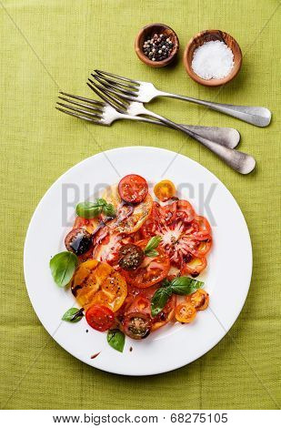 Ripe Fresh Colorful Tomatoes Salad With Olive Oil And Balsamic Vinegar On Green Background