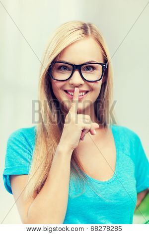 picture of smiling woman with finger on her lips