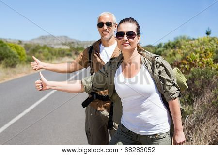 Hitch hiking couple standing on the side of the road with thumb out on a sunny day