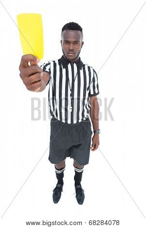 Serious referee showing yellow card on white background