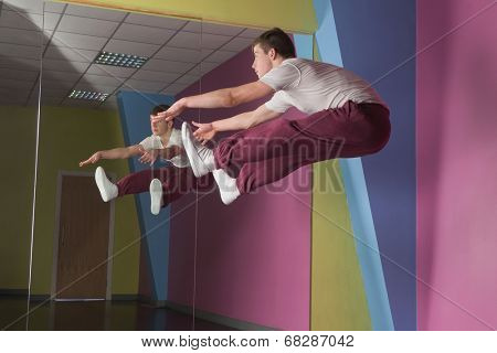 Cool break dancer mid air doing the splits in front of mirror in the dance studio
